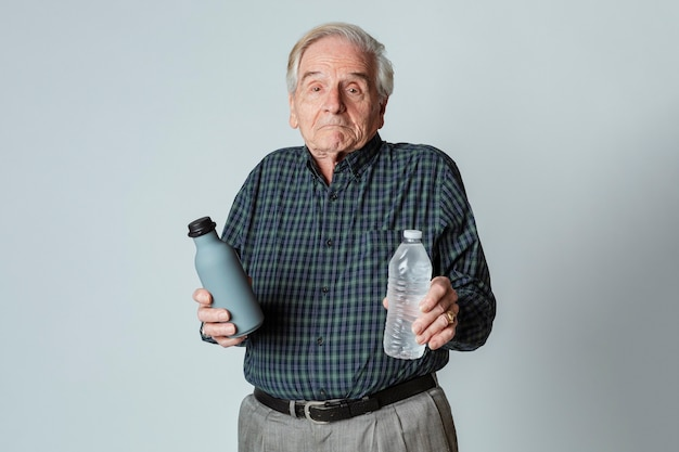 Puzzled senior man holding a reusable and a plastic water bottle