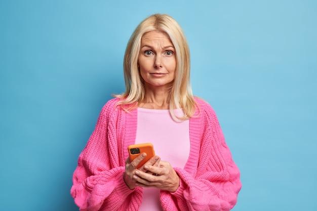 La donna senior perplessa tiene lo smartphone moderno nelle mani scarica la nuova applicazione ha una cattiva connessione mobile legge post sul social network vestito con un maglione lavorato a maglia.