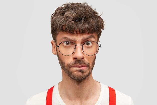 L'uomo serio con la barba lunga perplesso guarda sconcertato, incurva le labbra e sente esitazione, stringe le labbra, indossa gli occhiali