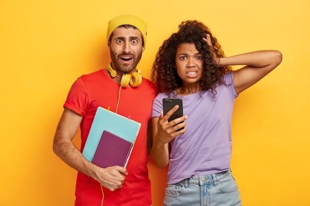 놀란 충격을받은 젊은 여성과 남성이 휴대 전화를 사용하고, 프로젝트 준비 기한이 있고, 함께 공부하고, 캐주얼 한 밝은 티셔츠를 입고, 끔찍한 표정으로 보입니다.