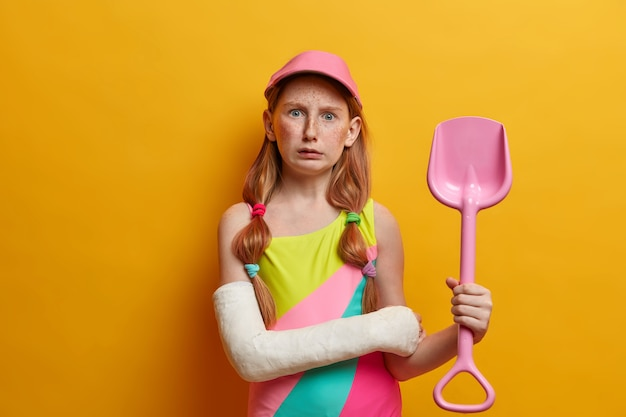 Puzzled small girl in cap and bathing suit, holds toy sand shovel, plays near sea at sandy beach, has bandaged arm after serious injury, isolated on yellow wall. childhood and summer rest concept