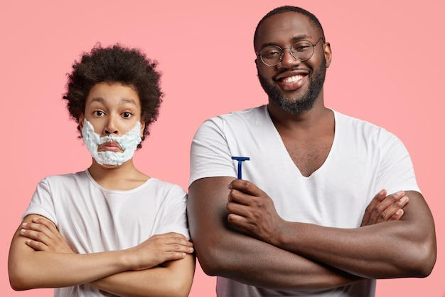 Puzzled son has foam on face, tries to imitate father, stands near dad, isolated over pink background.
