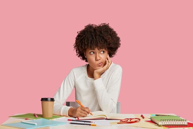 ピンクの壁に向かって机でポーズをとって困惑した学生の女の子