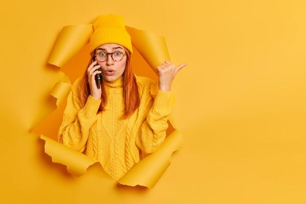 困惑した驚いたミレニアル世代の赤毛の女性が、カジュアルな服を着た親指で何か驚くべき点に反応し、スマートフォンを介して紙の穴を突破します