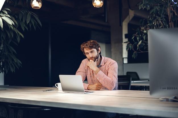 사무실에서 그의 작업 테이블에 앉아 의아해 사려 깊은 사업가. 사업 개념