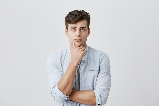 Puzzled thoughtful male student dressed in light blue shirt, holding hand under his chin, frowning face, looking upwards, being dissatisfied with problems at university, thinking over his mistakes.