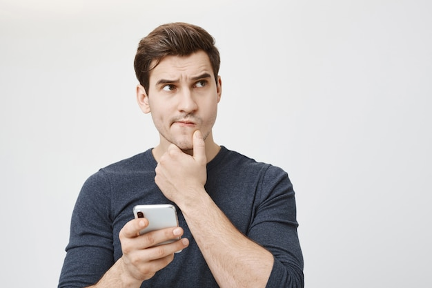 Puzzled thoughtful man thinking while holding smartphone