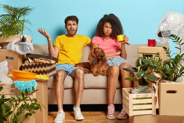 Puzzled tired married couple on sofa with dog surrounded with cardboard boxes