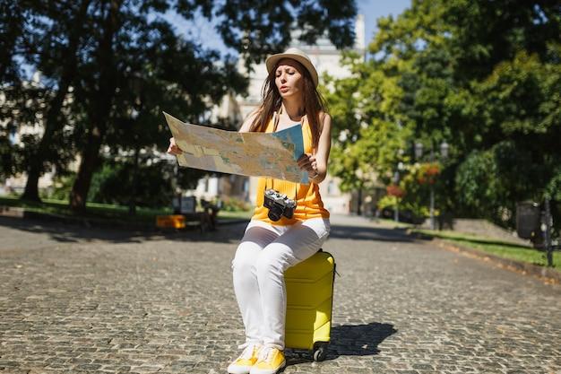 カジュアルな服装で困惑した旅行者の観光客の女性、屋外の都市地図検索ルートを保持しているスーツケースに座っている帽子。週末の休暇で旅行するために海外旅行する女の子。観光の旅のライフスタイル。