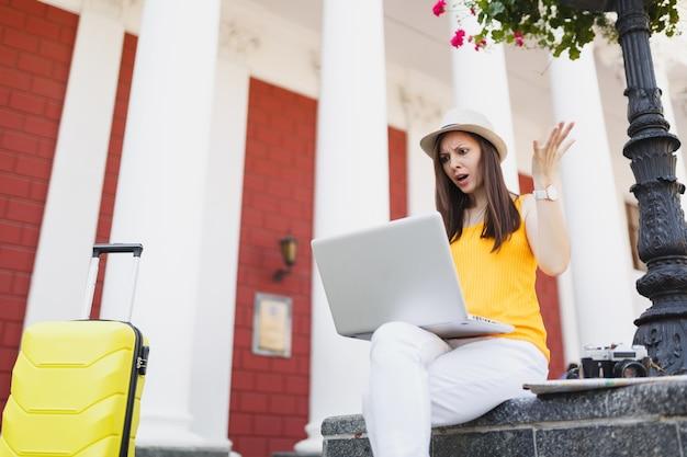 캐주얼한 옷을 입은 의아해한 여행자 관광 여성, 야외에서 노트북 컴퓨터 작업을 하며 여행가방을 든 모자. 주말 휴가에 해외 여행을 하는 소녀. 관광 여행 라이프 스타일.