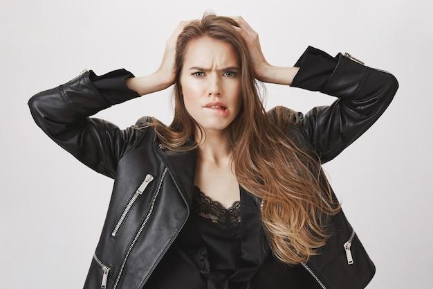 Donna confusa perplessa che morde labbro confusa, afferra la testa