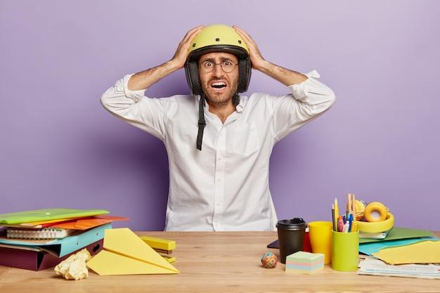 オフィスの机に座っている困惑した厄介な従業員