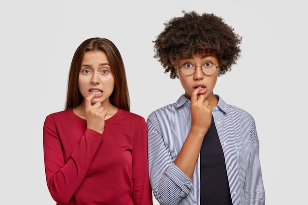 어리둥절한 두 소녀는 손가락을 물고, 우유부단 한 표정으로보고, 해결책을 찾고, 캐주얼 한 옷을 입고, 좌절감을 느끼며, 모델을 흰 벽에 기대고 있습니다. 다양성과 반응 개념