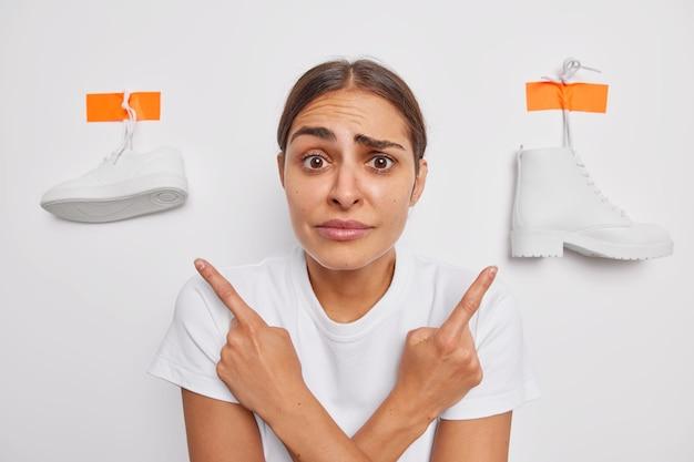 어리둥절한 젊은 여성이 운동화를 옆으로 가리키고 부츠는 흰 벽에 격리된 캐주얼 티셔츠를 입고 무엇을 입어야 할지 주저합니다