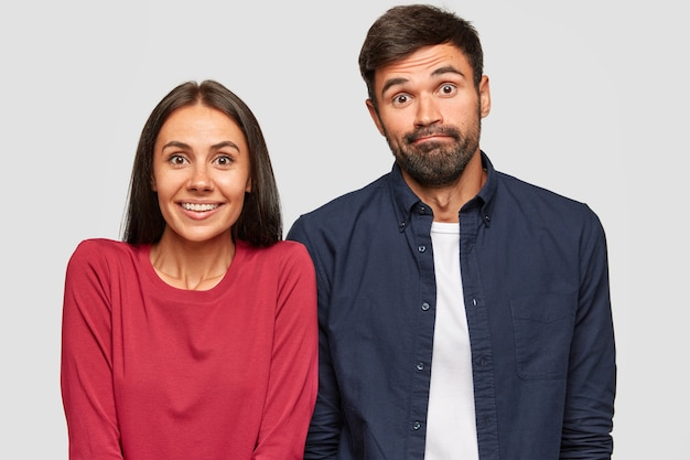 困惑した不確かな若い女性と男性がカメラで疑わしい表情で見て、決定を下すようにしてください