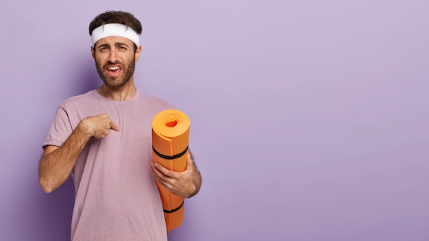 Puzzled unshaven man points at himself with indignation, wears white headband and casual purple t shirt, asks trainer whether exactly he should do exercise, carries mat