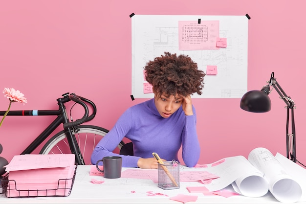 Puzzled woman architect improves graphics corrects mistakes busy working on archiectural project and having deadline poses at desktop has deadline surrounded with papers tries to solve problem