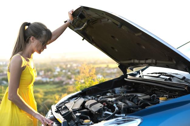 Озадаченная женщина-водитель стоит возле своей машины с поднятым капотом и осматривает сломанный двигатель.