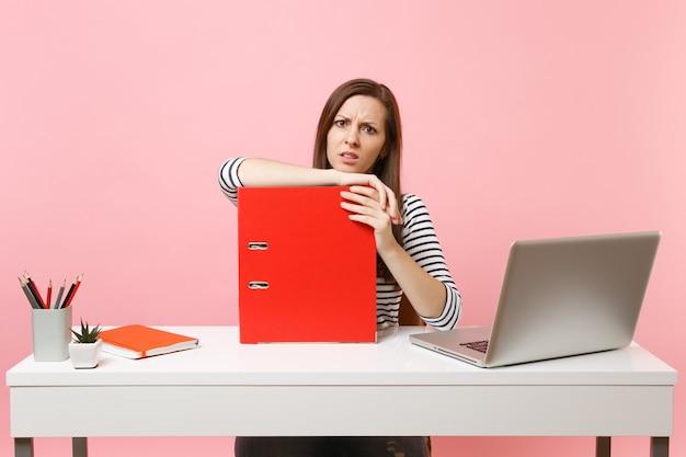종이 문서가 있는 빨간색 폴더에 기대어 노트북을 들고 사무실에 앉아 프로젝트 작업을 하는 어리둥절한 여성