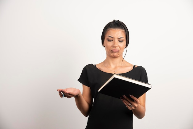Puzzled woman looking at notebook on white wall.