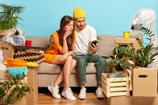 Puzzled woman and man look at smartphone device, relocate in new apartment, search furniture for their flat in online shop