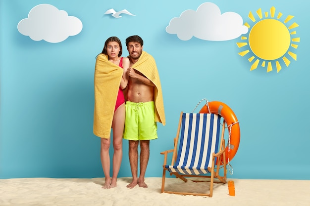 Puzzled woman and man tremble under towel, feel cold, try to warm after swimming