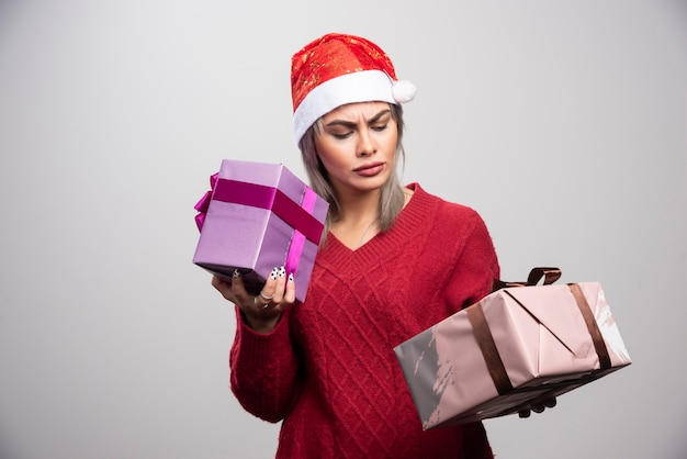 Puzzled woman in santa hat looking at christmas gifts.