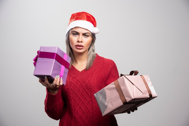Puzzled woman in santa hat with christmas gifts looking at camera.