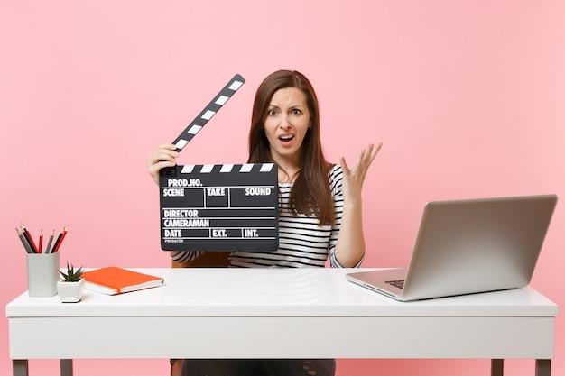 Озадаченная женщина, разводя руками, держа классическую черную пленку, снимающую с хлопушкой, работая над проектом, сидя в офисе с ноутбуком
