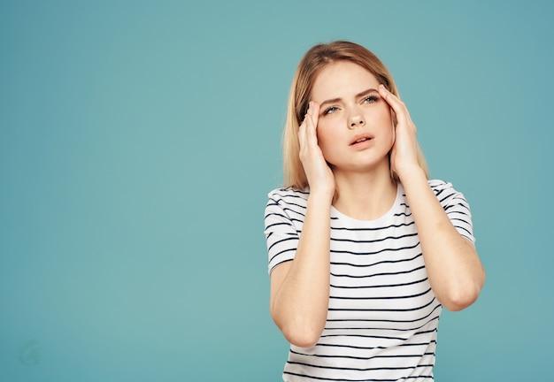 Озадаченная женщина касается ее лица руками на синей стене модели стрессовых эмоций.
