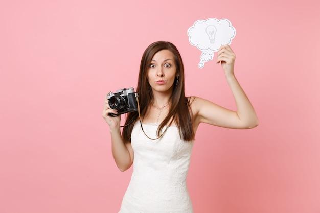 Una donna perplessa in abito bianco tiene in mano una macchina fotografica vintage retrò, dice nuvoletta nuvola con una lampadina che sceglie il personale, fotografo