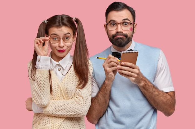 Puzzled wonk guy with lipstick on cheek, writes down information in notepad, pretty european girl keeps hand on frame of big spectacles