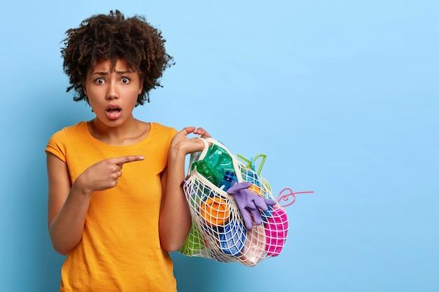 困惑した心配している女性ボランティアがプラスチック廃棄物を拾う