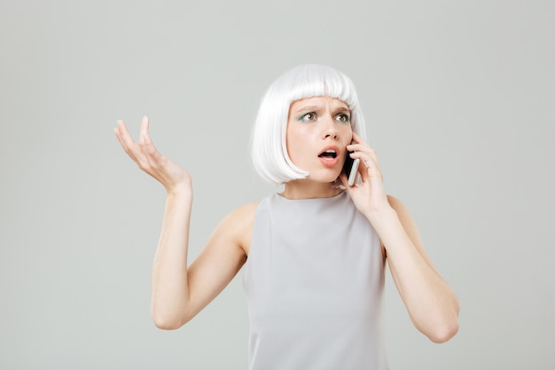 Puzzled worried young woman in blonde wig standing and talking on mobile phone