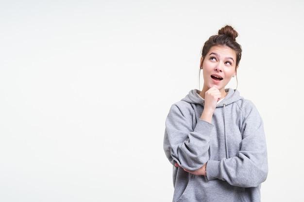 Озадаченная молодая привлекательная брюнетка с прической задумчиво смотрит вверх и держит подбородок с поднятой рукой, стоя на белом фоне