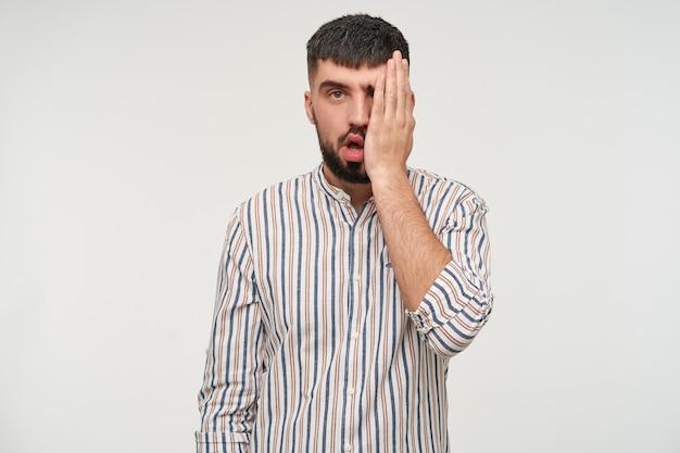흰 벽 위에 서있는 동안 줄무늬 셔츠를 입고 수염을 가진 의아해 젊은 매력적인 짧은 머리 갈색 머리 남자, 피곤하게 보면서 그의 얼굴에 손바닥을 유지