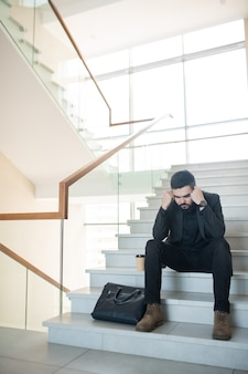 Puzzled young bearded businessman in black suit sitting on stairs with takeout coffee cup and holding head in hands
