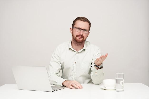 白い背景に座って、不快な顔でカメラを見ながら彼の手のひらを上げたまま眼鏡をかけた若いひげを生やしたビジネスマン