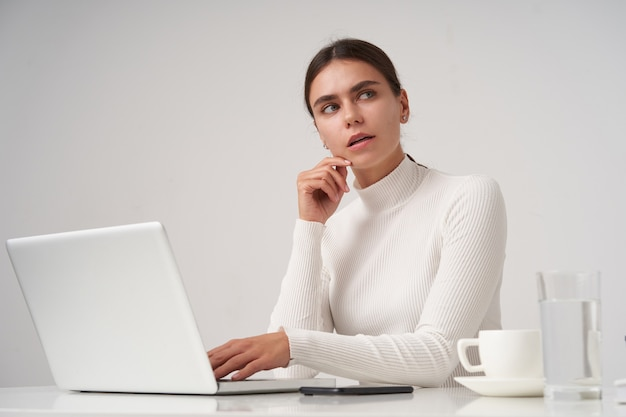 Puzzled young beautiful dark haired lady with natural makeup touching her face with raised hand and looking thoughtfully, working at modern office with laptop over white wall