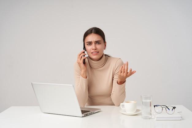 Giovane signora dai capelli scuri dagli occhi blu perplessa che indossa abiti formali mentre è seduto in ufficio con un laptop moderno, aggrottando le sopracciglia mentre parla al telefono