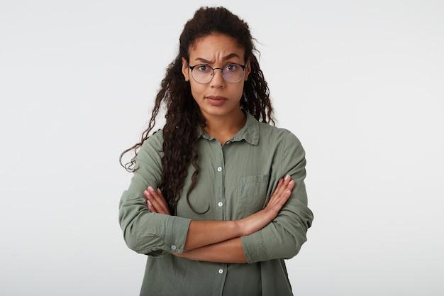 Giovane donna riccia dai capelli lunghi dagli occhi marroni perplessa con la pelle scura che tiene le mani incrociate mentre guarda confusamente la telecamera con il sopracciglio alzato, in posa su sfondo bianco