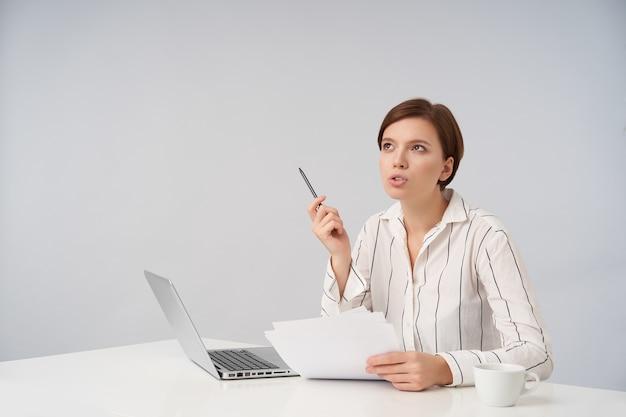 Озадаченная молодая шатенка бизнес-леди с короткой модной стрижкой в строгой одежде позирует на белом, задумчиво смотрит вверх и держит ручку в поднятой руке