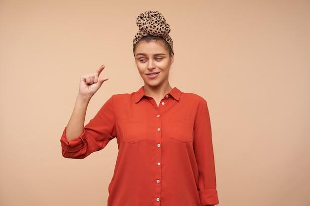 Perplessa giovane signora dai capelli castani che indossa la fascia in nodo mentre si trova sul muro beige, guardando confusamente sulla sua mano mentre mostra piccole dimensioni con le dita