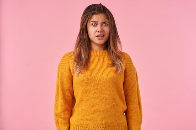 暖かいニットのマスタードセーターでピンクにポーズをとっている間、不思議な眉を上げて額にしわを寄せている困惑した若い茶色の髪の女性