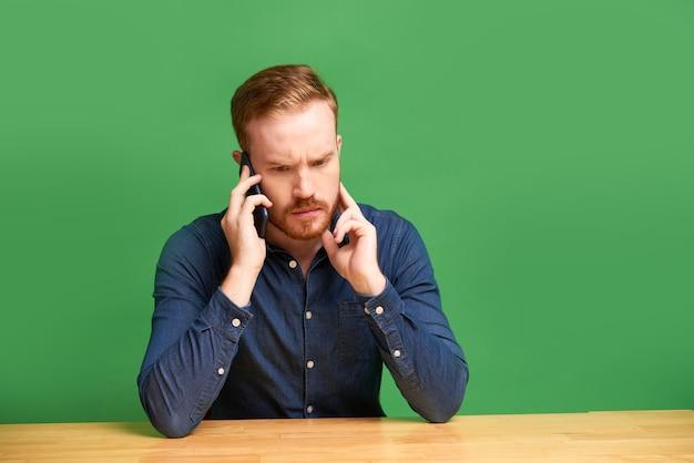 緑の背景に木製のテーブルに座って、電話で話しているひげを持つ困惑した若い白人男性