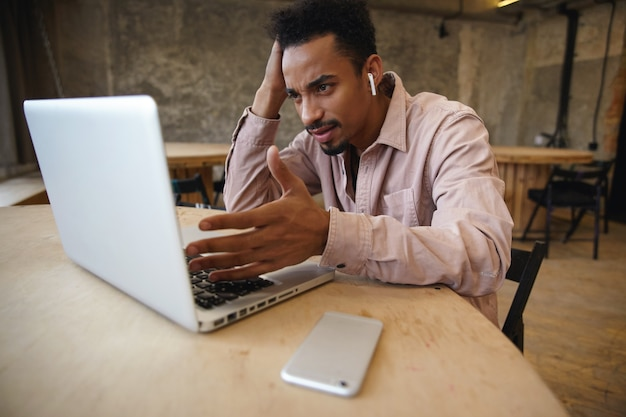 Perplesso giovane uomo d'affari dalla pelle scura con la barba che lavora a distanza con il suo laptop e smartphone, seduto al tavolo in camicia beige, guardando lo schermo con viso serio e testa pendente a portata di mano