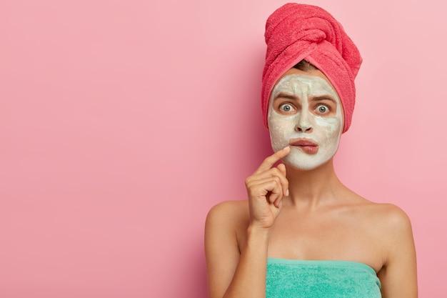 의아해하는 젊은 여성은 입술을 물고, 얼굴에 점토 마스크를 바르고, 수건에 토플리스를 서고, 분홍색 벽에 모델을 세우고, 미용 치료를 받고, 자신을 돌 봅니다. 사람, 웰빙 및 필링 개념