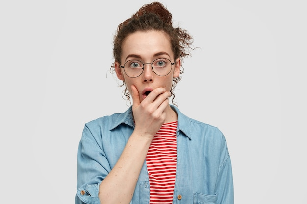 混乱した表情で困惑した若いそばかすのある女性、あごを保持し、困難な状況で問題を解決しようとし、結び目で巻き毛をとかし、カジュアルなシャツを着て、白い壁にポーズをとる