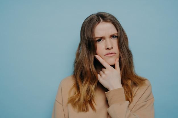 カジュアルな薄茶色のセーターを着て、青いスタジオの背景に立っているあごに手を握っている間、懸念と関心を示す太い波状のオンブル髪の困惑した少女