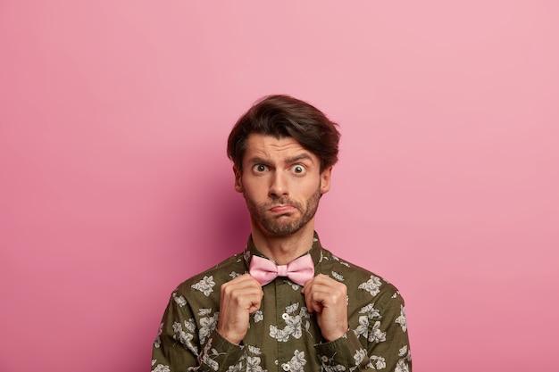 困惑した若い男は眉を上げ、剛毛を持ち、蝶ネクタイを調整し、モダンなプリントのファッショナブルなシャツを着て、上品な服を着て、バラ色の空間に立ち向かいます。人